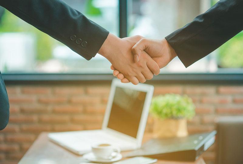 Dos personas cierran un trato con un apretón de manos.